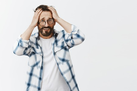 Foto de Man cannot remember how he got home after party, standing in crooked glasses, touching head and frowning, feeling headache from hangover, standing unhappy and gloomy over gray background - Imagen libre de derechos