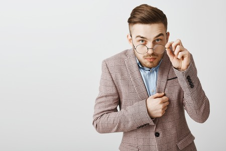 Photo for Studio shot of funny nerdy male office worker in trendy jacket with trendy hairstyle looking from under glasses touching rim of eyewear being intrigued and interested while hearing secret of friend - Royalty Free Image