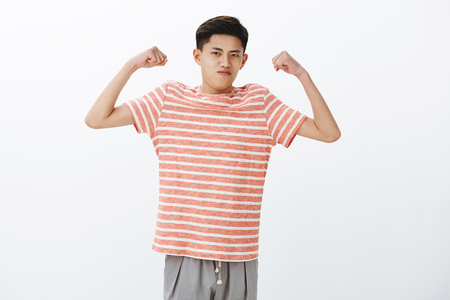 Foto de Look how strong I am. Portrait of self-assured funny young slim asian guy raising hands to show biceps or muscles, starting working out, straining and holding breath to look masculine - Imagen libre de derechos