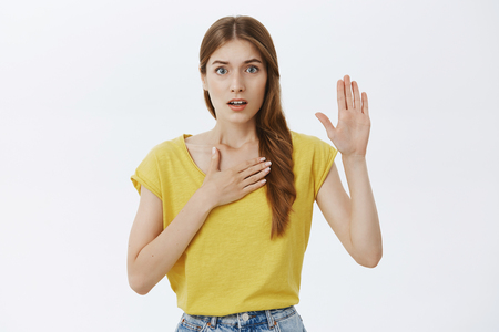 Foto de I swear telling truth. Portrait of worried and nervous cute timid young girl holding palm on chest and raising hand swearing to be honest facing judge or trial standing against gray background - Imagen libre de derechos