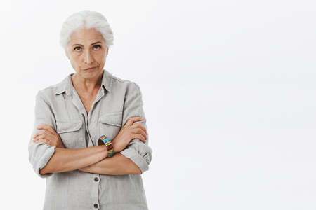 Photo pour Displeased angry elderly mother with grey hair looking from under forehead with irritated expression pursing lips crossing arms over chest scolding granddaughter - image libre de droit