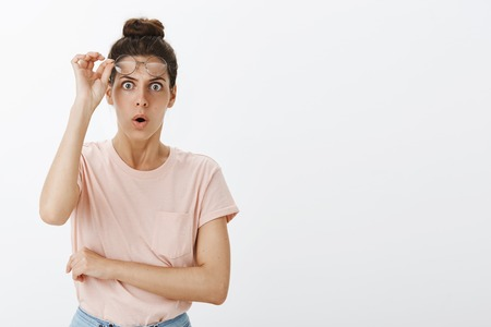 Foto de Portrait of stunned and shocked woman in stupor taking off glasses and dropping jaw as looking at disturbing and unacceptable behaviour standing shook and intense - Imagen libre de derechos