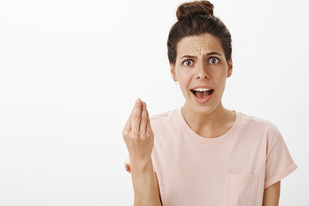 Foto de Portrait of bothered and annoyed young woman arguing expressing own point of view why she fed up shaking hand in italian gesture frowning and complaining at camera - Imagen libre de derechos