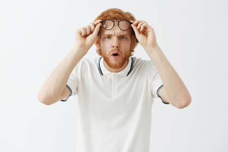 Photo for Guy getting closer look at confusing thing. Intense doubtful and questioned redhead intrigued guy with beard taking off glasses holding them on forehead folding lips and opening mouth from interest - Royalty Free Image
