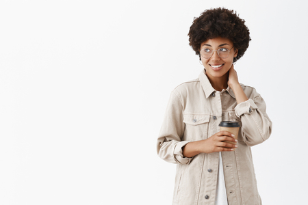 Photo pour Getting ready to start working productively after great energetic coffee. Shy african american female office worker in shirt and glasses touching neck, gazing left with smile and holding paper cup - image libre de droit