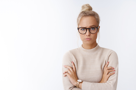 Photo pour Woman showing disbelief looking suspicious not believing single word crossing arms over chest doubtful raising eyebrow with pokerface standing unimpressed and bothered over white background - image libre de droit