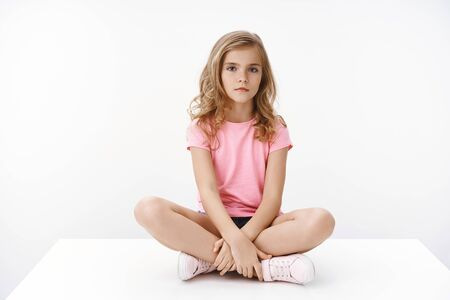 Photo for Serious indifferent cute blond little girl sitting on floor, legs crossed, look bored and unamused, boring homesick, unwilling do homework, pose white background in pink t-shirt and shorts - Royalty Free Image