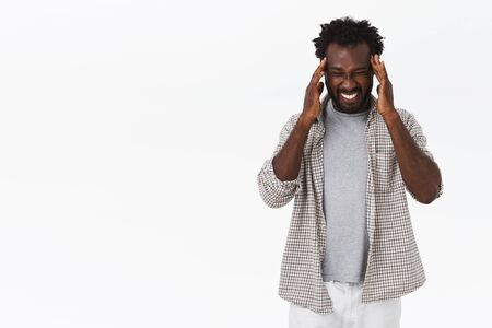 Foto de African-american bearded guy suffering unbearable headache, touching temples, squinting and making grimace, feeling painful migraine, standing dizzy, need painkillers, stand white background - Imagen libre de derechos