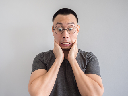 Photo pour Shocked and surprised freelance Asian man with funny face. - image libre de droit