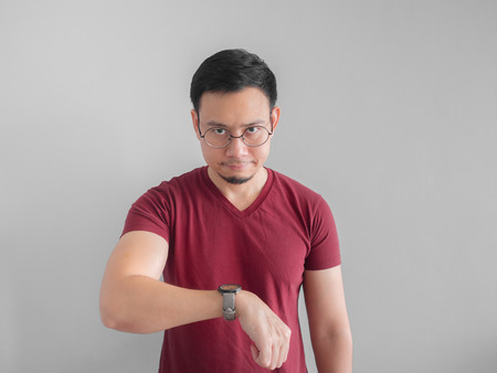 Foto de Angry and unpleasant face of Asian man is looking at his watch waiting for someone. - Imagen libre de derechos
