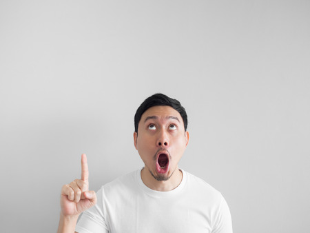 Photo pour Shocked face of Asian man in white shirt on grey background. - image libre de droit