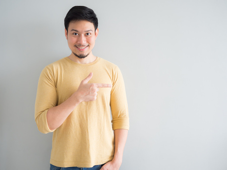 Photo for Asian man in yellow t-shirt excited to point and present an empty space background. - Royalty Free Image