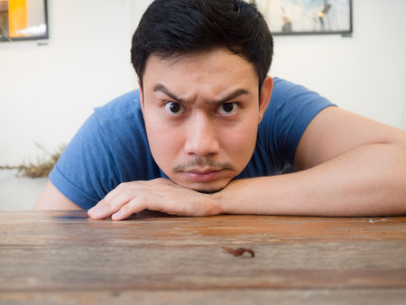 Photo for Boring and serious face Asian man rest his chin on his hand. - Royalty Free Image
