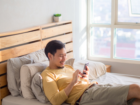Photo for Asian man using smartphone in his bed in the morning. - Royalty Free Image