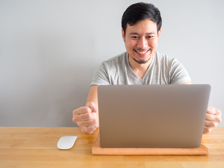 Photo for Smile Asian man is feeling happy with his work in the laptop. - Royalty Free Image