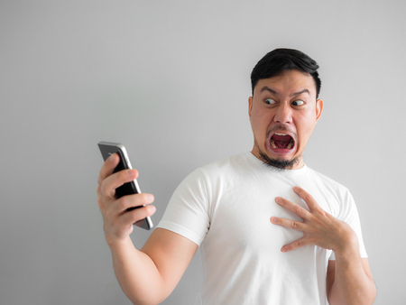 Photo for Shocked and scary face of Asian man get yelled from smartphone.  See something scary in smartphone. - Royalty Free Image