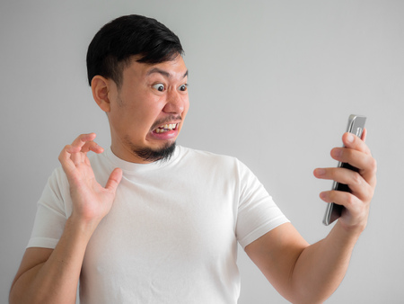 Foto de Shocked and scary face of Asian man get yelled from smartphone.  See something scary in smartphone. - Imagen libre de derechos