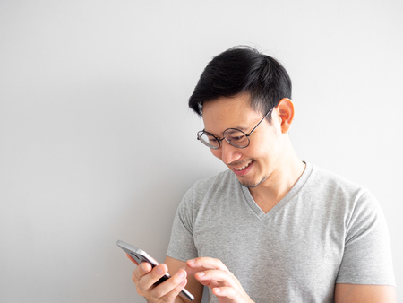Photo for Happy Asian man is using smartphone. Concept of using social media on mobile phone. - Royalty Free Image