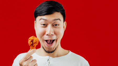 Photo for Funny face Asian man is eating fried chicken deliciously. - Royalty Free Image