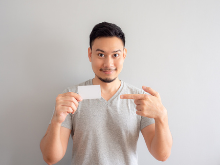 Photo pour Happy Asian man is showing a white credit card. - image libre de droit
