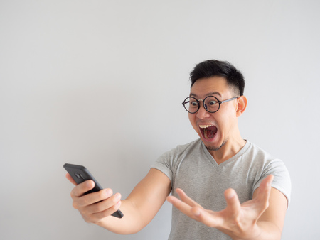 Photo pour Wow face of Asian man shocked what he see in the smartphone on isolated grey background. - image libre de droit
