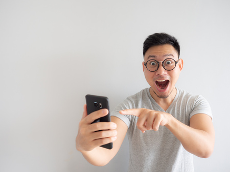 Foto de Wow face of Asian man shocked what he see in the smartphone on isolated grey background. - Imagen libre de derechos