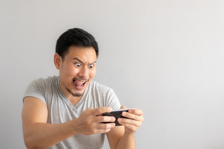 Foto de Crazy and funny face of Asian man addicted to play mobile game. - Imagen libre de derechos