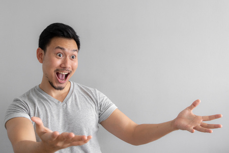 Foto de Wow and shocked face of Asian man point to present an empty space of content. Advertising model concept. - Imagen libre de derechos