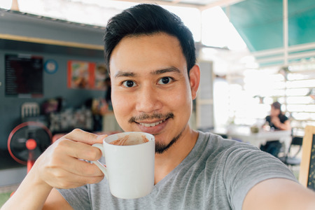 Photo pour Selfie portrait of happy Asian man drink mug of hot coffee. - image libre de droit