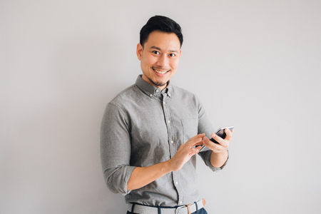 Foto de Happy smile face of handsome Asian man use smartphone. - Imagen libre de derechos
