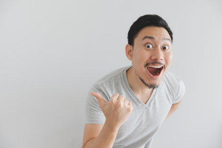 Photo pour Wow and surprised face of Asian man in grey t-shirt with hand point on empty space. - image libre de droit
