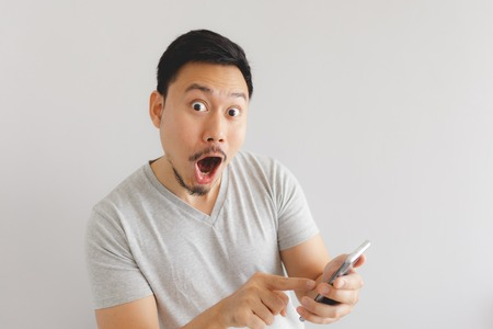 Photo pour Wow face of Asian man in grey t-shirt get surprised on the smartphone. - image libre de droit
