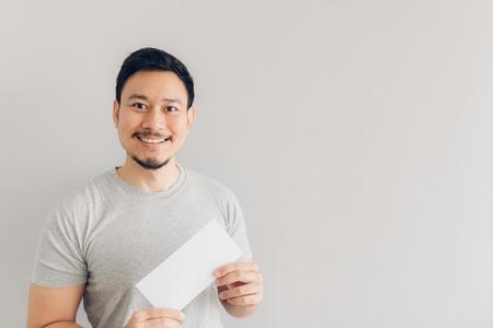 Foto de Asian man is happy with the white mail message or the bill. - Imagen libre de derechos