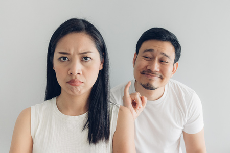Photo pour Sulk and reconcile Asian couple lover in white t-shirt and grey background. - image libre de droit