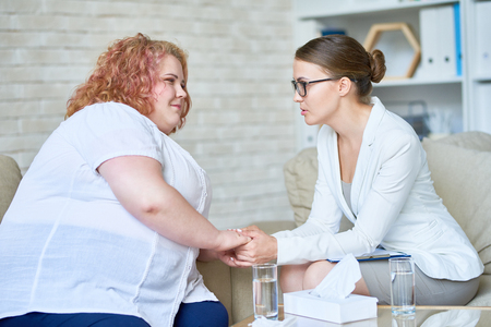 Foto de Portrait of beautiful female psychiatrist  offering psychological support to obese young woman holding hands and comforting her during therapy session on mental issues in doctors office. - Imagen libre de derechos