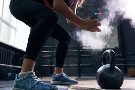 Photo for Side view closeup of unrecognizable young woman rubbing her hands with talk puffing cloud preparing to lift kettlebells during crossfit workout in modern gym - Royalty Free Image
