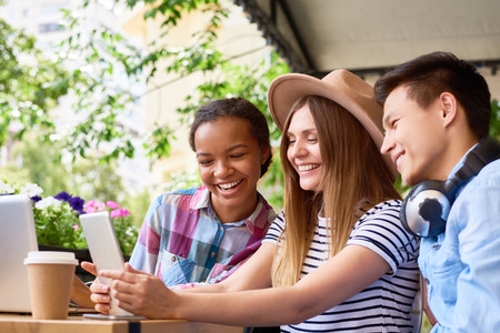Photo for Multi-ethnic group of smiling young people using laptop and digital tablet in outdoor cafe on sunny summer day - Royalty Free Image