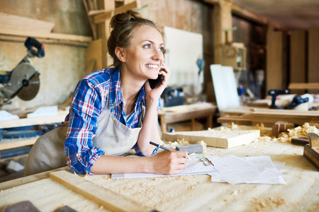 Foto de Cheerful young carpenter discussing order details with her customer on smartphone and taking necessary notes, interior of spacious workshop on background - Imagen libre de derechos