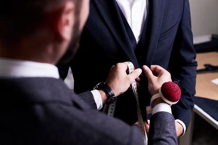 Foto de Over shoulder view of bearded fashion designer fitting bespoke suit to model, close-up shot - Imagen libre de derechos