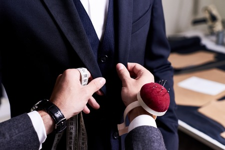 Foto de Closeup of tailor fitting bespoke suit to model, hands with tape measure and pin cushion fixing jacket on male model - Imagen libre de derechos