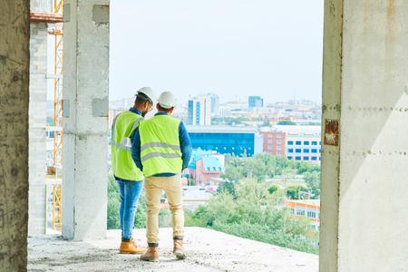 Photo pour Men in hardhats at construction site of apartment building - image libre de droit