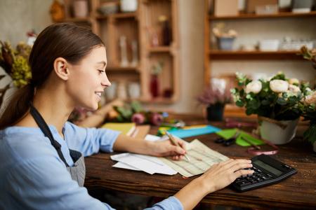 Photo pour Woman doing Accounting in Shop - image libre de droit