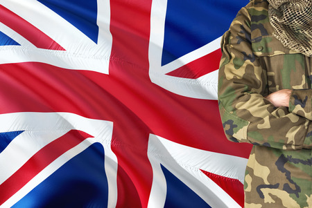 Foto de Crossed arms British soldier with national waving flag on background - United Kingdom Military theme. - Imagen libre de derechos