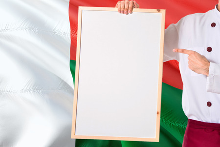 Foto de Malagasy Chef holding blank whiteboard menu on Madagascar flag background. Cook wearing uniform pointing space for text. - Imagen libre de derechos