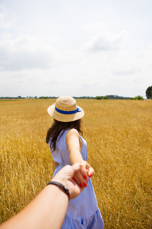 Photo for a girl in a blue dress is standing with her back in a wheat field. - Royalty Free Image