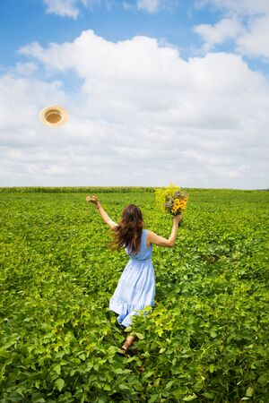 Photo for beautiful girl stands in the field with a bouquet of yellow flowers and throws her hat to the sky. - Royalty Free Image