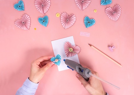Foto de Scrapbooking master class. Diy. Make a Valentines day card whith paper hearts. Women's hobby. Craft supplies on the table - Imagen libre de derechos