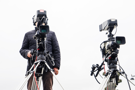 Photo for cameraman with his video camera shooting outdoor in the city - Royalty Free Image