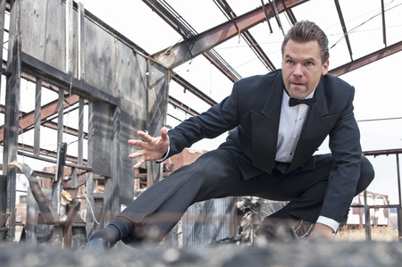 Photo pour Handsome tough Caucasian man in black tuxedo poses in action stunt scene in destroyed warehouse - image libre de droit