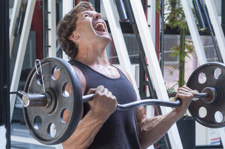 Photo pour Muscular Caucasian man in tank top painfully struggles to complete repetition of arm curls in gym - image libre de droit
